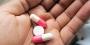 A hand holding three pills.