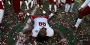 A Temple football player laying on the confetti covered field.