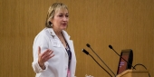 Darilyn Moyer wearing a lab coat and speaking at a podium.