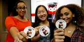 """Three students each holding a sticker that says """"I donated."""""""