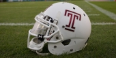 """A white Temple football helmet with a cherry Temple """"T"""""""
