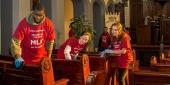 Student volunteers clean pews inside the Berean church.