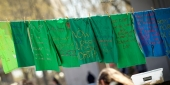Green t-shirts with messages hanging from a clothesline in Founder's Garden.