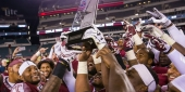 Temple's football team holding the AAC East Conference Division title trophy.