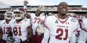 Temple football players smiling and celebrating on the field after a big win.