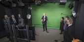A group of administrators looking at the green screen set up in the film studio.