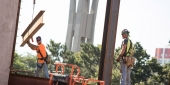 Construction workers place steel beams on Temple's new library.