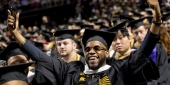 A graduate celebrating at Temple's Commencement