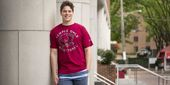 Marcus Forst wearing a Temple basketball shirt in front of Alter Hall