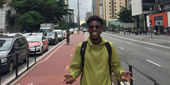 Xavier Burke standing at the center of a busy road in Sao Paulo, Brazil.