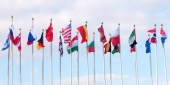A collection of international flags flying from flagpoles.