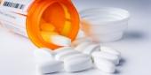 Prescription pills spilling out of a prescription bottle.