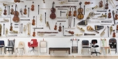 A large display of musical instruments and chairs hanging on a gallery wall.
