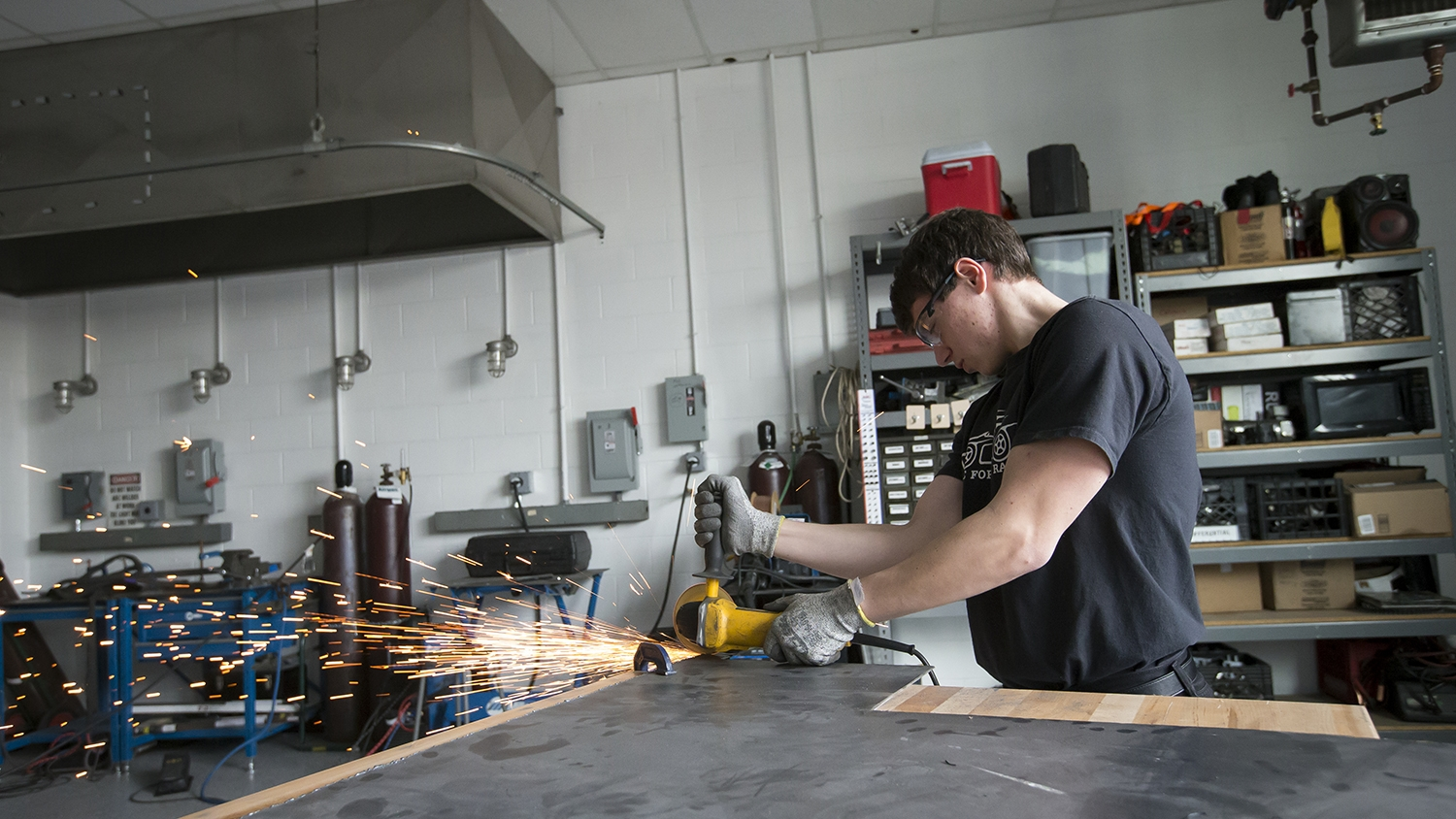 Sparks flying as a student uses a saw.