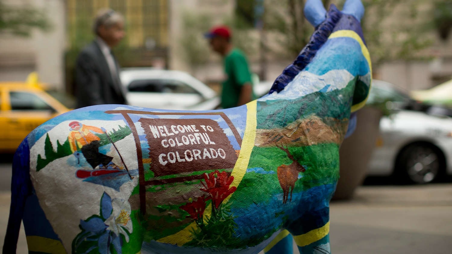 A donkey painted with visual elements representing Colorado.