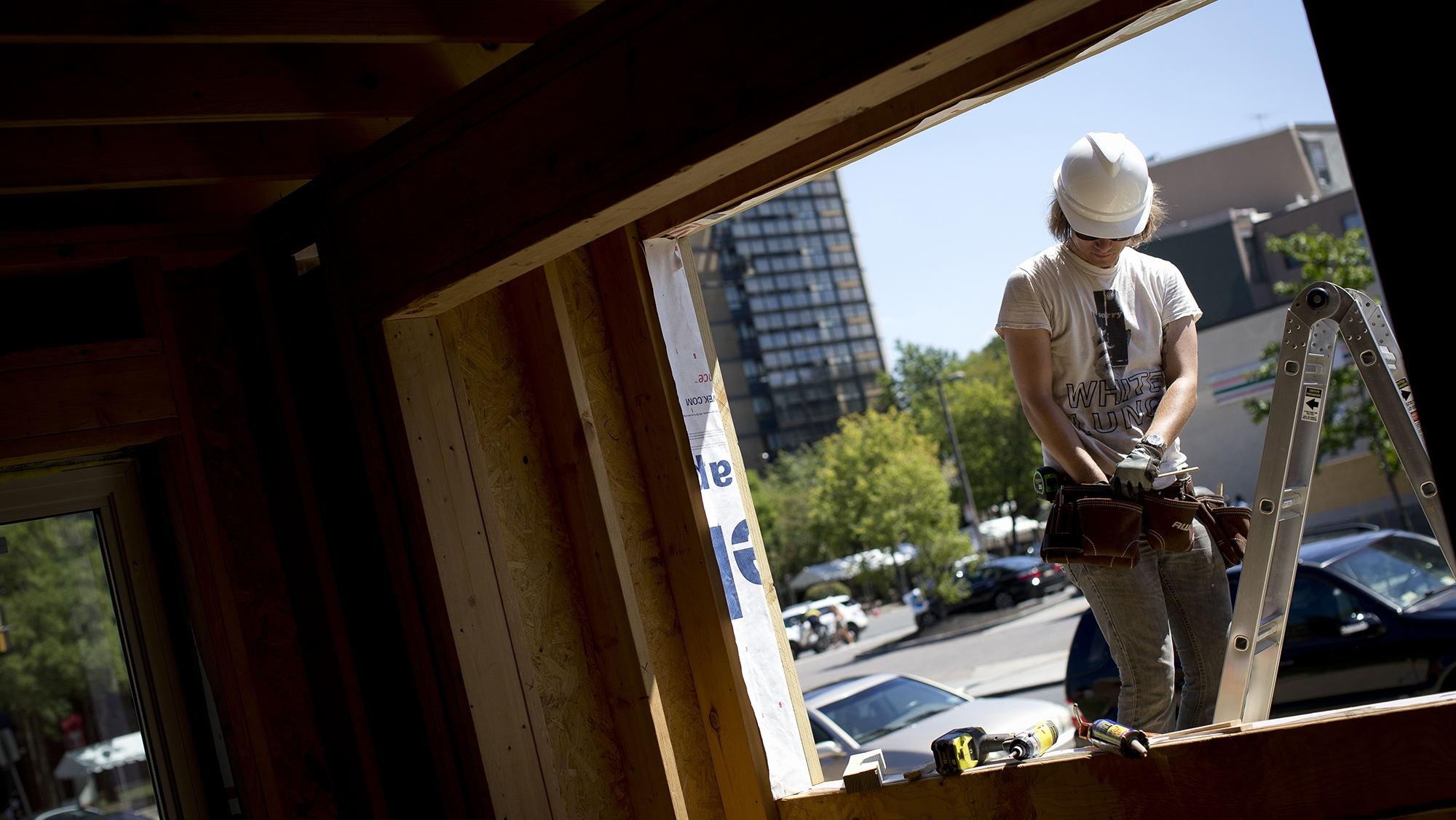 A construction worker as seen from the inside of the tiny house.