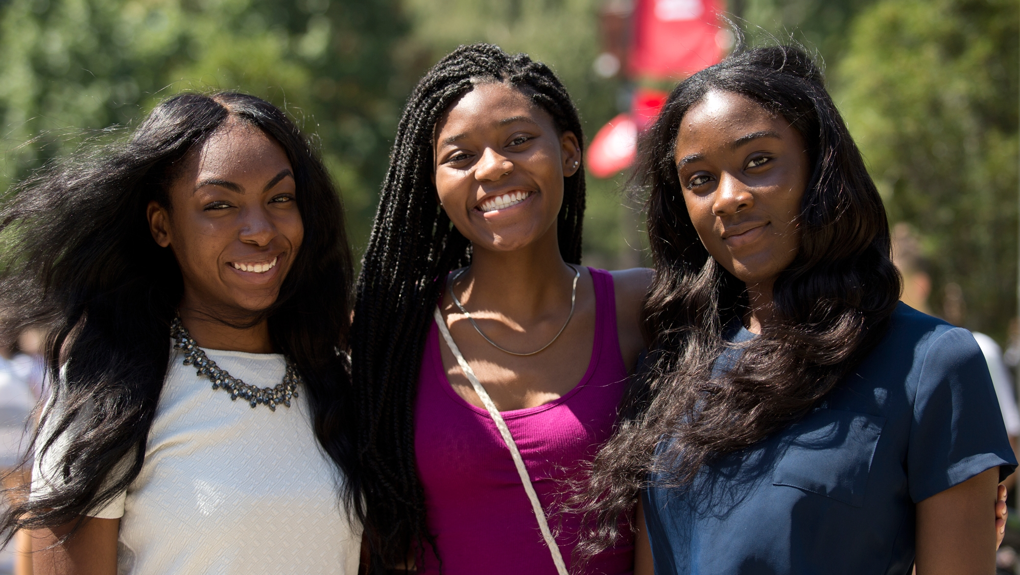 Three women standing near the Bell Tower on Temple's Main Campus.