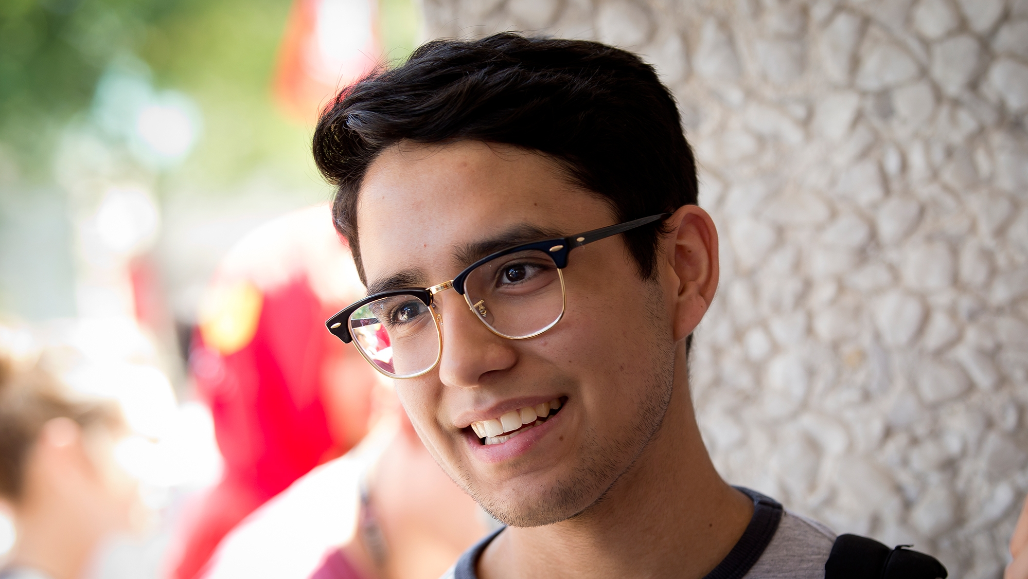 A man wearing glasses and smiling at the new student BBQ on Main Campus.