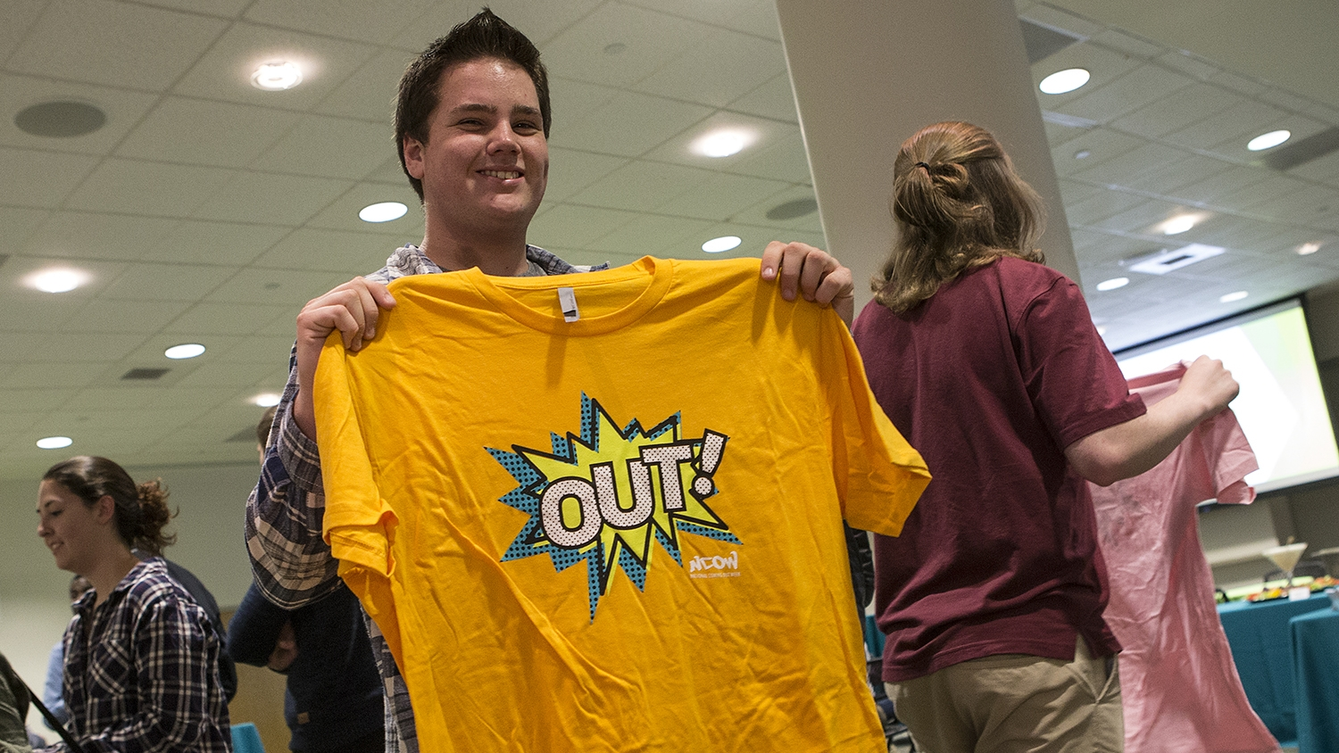 "A student holding a yellow t-shirt with the words ""out"" printed on it."