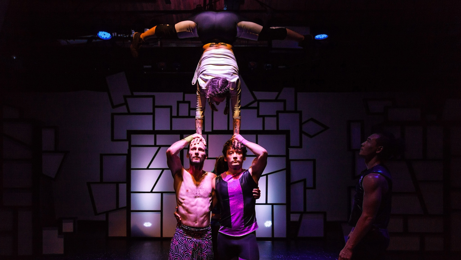 A woman doing a handstand supported by two men.