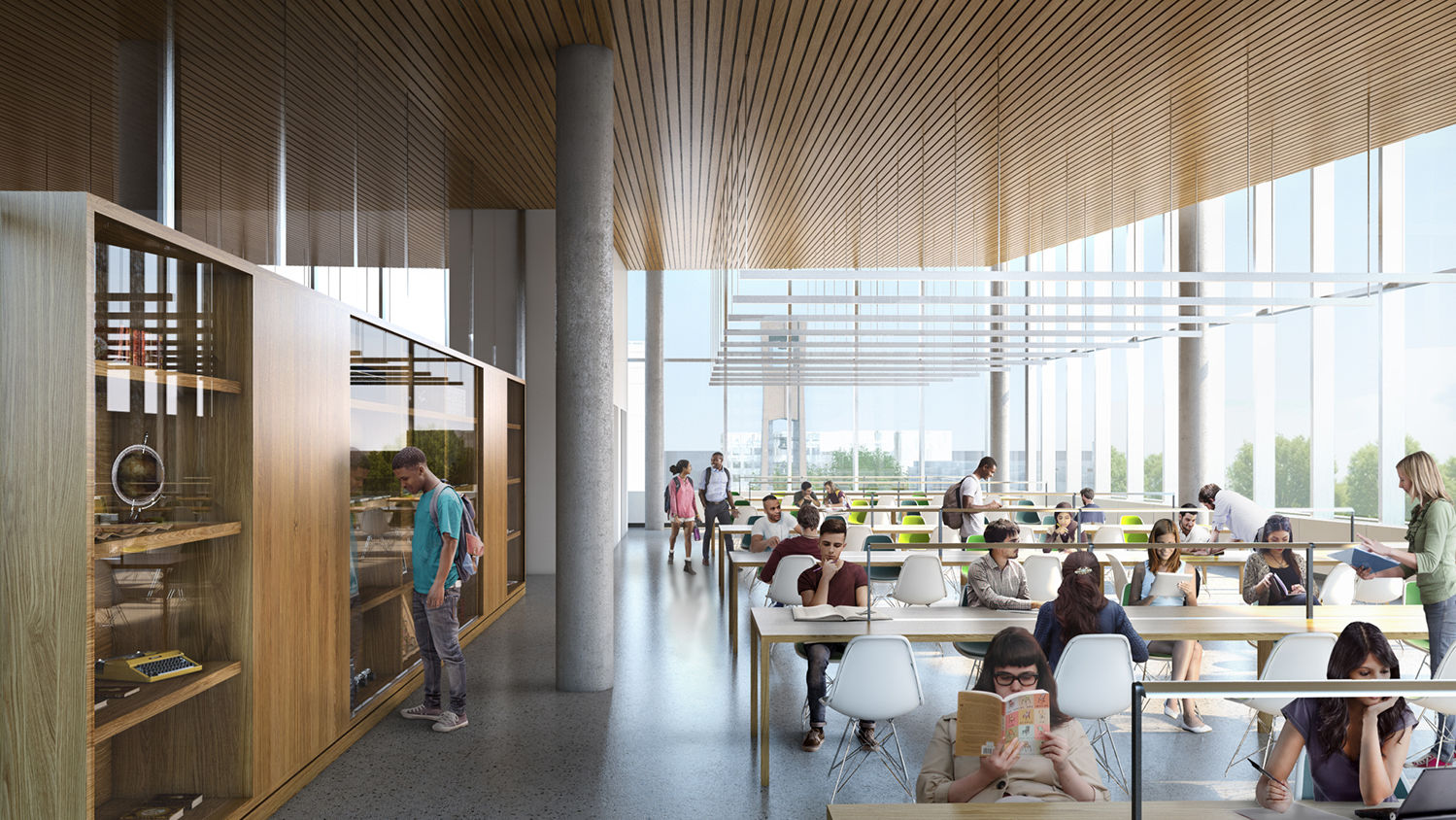 Students sitting at long tables in front of a wall of windows on an upper floor of the new library.