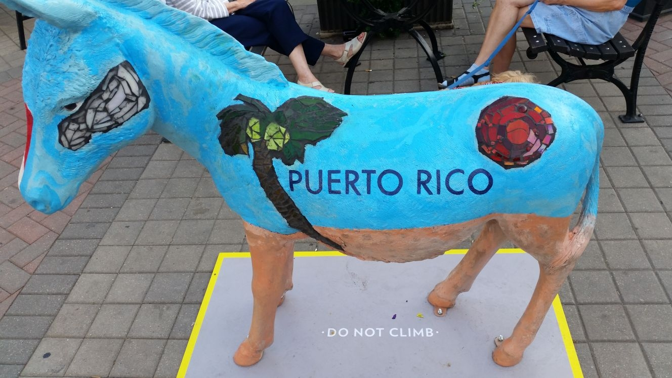 A donkey painted with visual elements representing Puerto Rico.