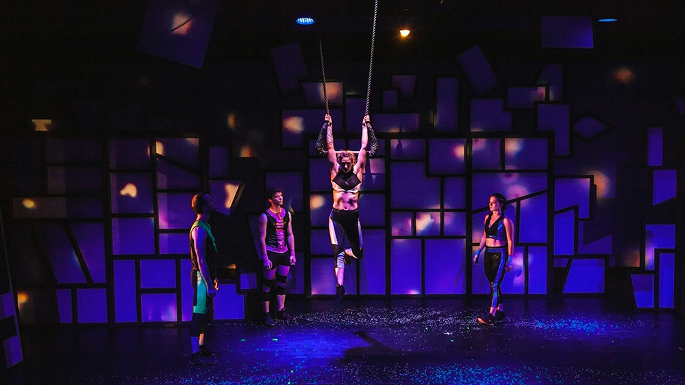 A woman hanging from a trapeze bar.