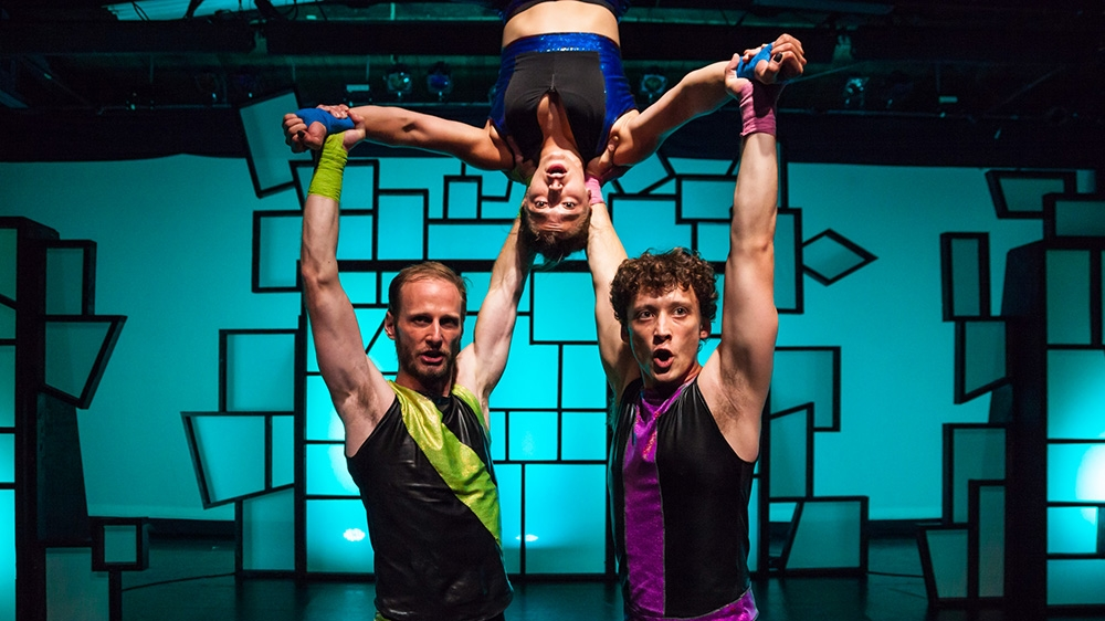 Two male dancers holding a female dancer upside down.