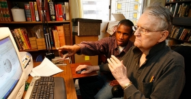 a student helping a man at a computer