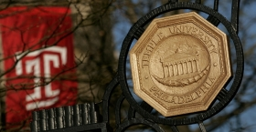 """the iron gate leading onto Temple's Main Campus and a red Temple """"T"""" flag."""