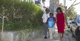 Two women and a young girl walking together through a residential neighborhood in North Philadelphia.