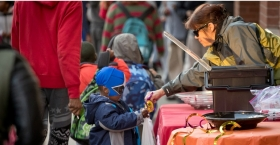 Woman handing candy to a little boy in costume during Avenue of Treats event