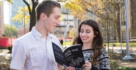 Adam Gasiewski standing with Emily Beck, who is holding a copy of Milk and Vine