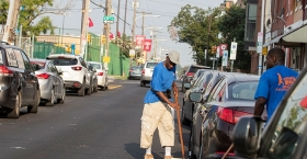men cleaning the street near Temple's campus