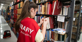 a student labeling books in Paley Library