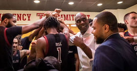 Aaron McKie and coaches, players huddle