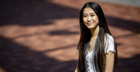 Michelle Wu wearing a white shirt and smiling outside of a building.