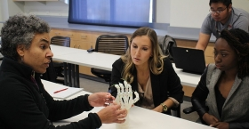 Students working with a prosthetic hand in a classroom.