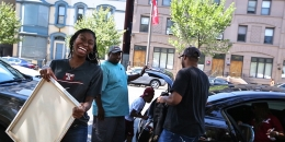 A woman in a Temple T-shirt smiling as she unpacks a car during move in.