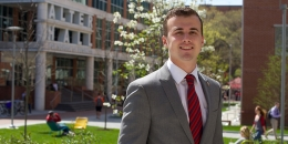 A man in a red tie standing in front of Temple University's Alter Hall.